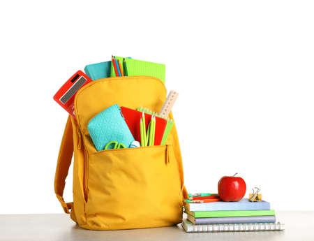 Farbrucksack mit Briefpapier auf weißem Hintergrund. Fertig für die Schule