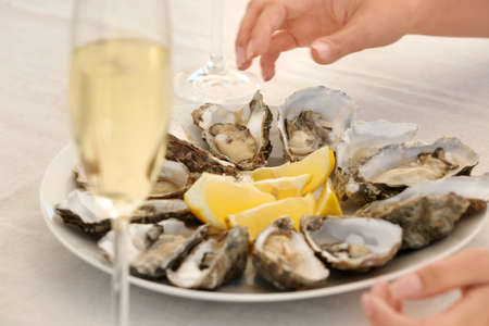 Woman with fresh oysters at table, focus on hands
