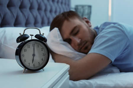 Alarm clock on table and young man sleeping in bed at night Archivio Fotografico - 107070230