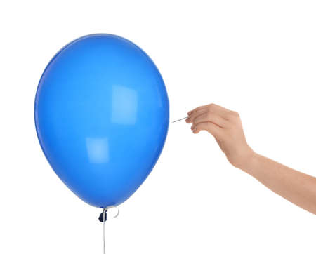 Woman piercing blue balloon on white background