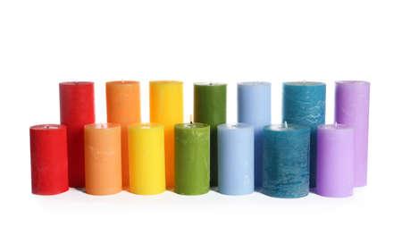 Diferentes velas de cera de colores sobre fondo blanco. Foto de archivo