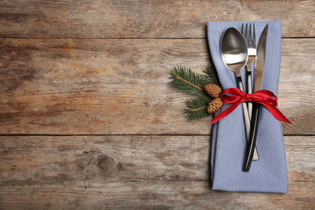 Cutlery and napkin on wooden background, top view. Table setting