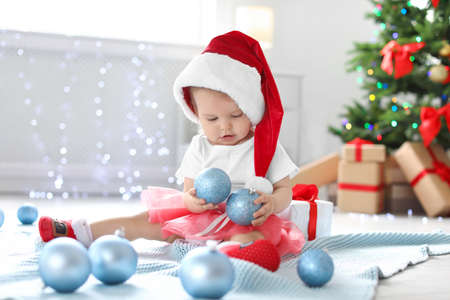 Cute baby in festive costume playing with Christmas decor on floor at home