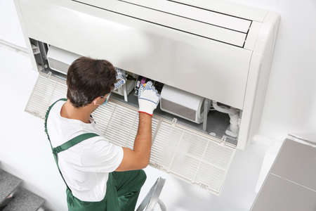 Young male technician repairing air conditioner indoors