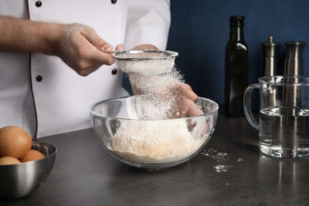 Man sprinkling dough for pastry with flour on table