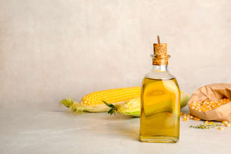 Bottle of corn oil and fresh cobs on table against light wall