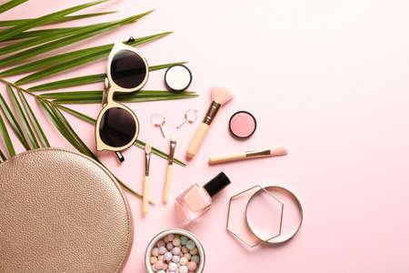 Flache Laienkomposition mit Produkten für dekoratives Make-up auf pastellrosa Hintergrund