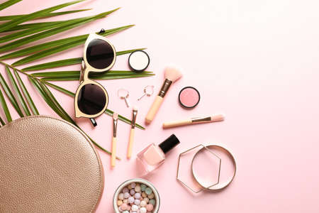 Flat lay composition with products for decorative makeup on pastel pink background
