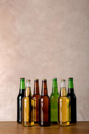 Bottles with different beer on table against color background