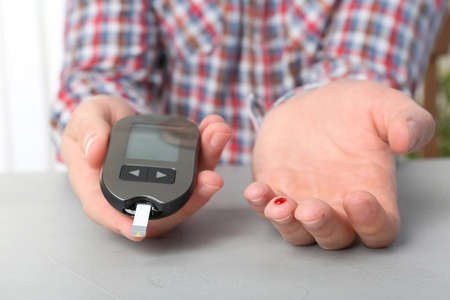 Man checking blood sugar level with glucometer at table. Diabetes test Banque d'images