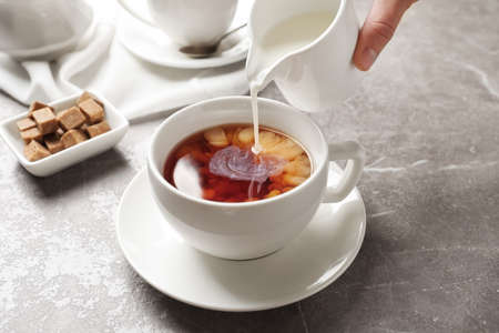 Pouring milk into cup of black tea on table Stockfoto - 106685151