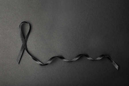 Black ribbon and space for text on dark background, top view. Funeral accessory Stock Photo