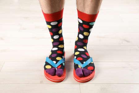 Uomo in calzini e pantofole sul pavimento, primo piano
