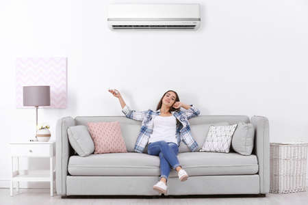 Young woman operating air conditioner while sitting on sofa at home