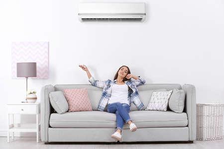 Młoda kobieta pracuje klimatyzator siedząc na kanapie w domu