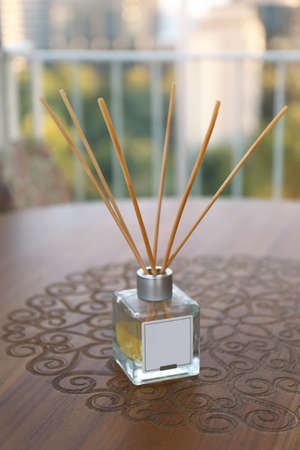 Reed air freshener on wooden table in room Stock Photo