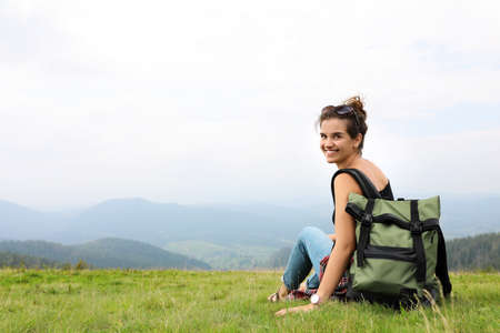 Woman with backpack in wilderness on cloudy day