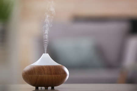 Aroma oil diffuser lamp on table against blurred background Standard-Bild