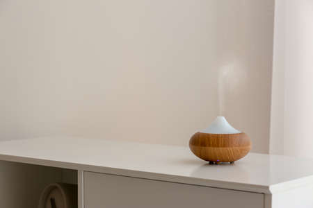 Aroma oil diffuser lamp on cabinet against light background