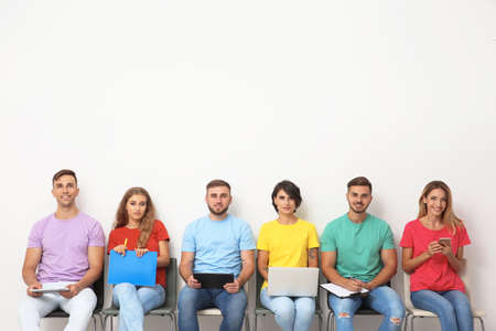 Group of young people waiting for job interview near light wall