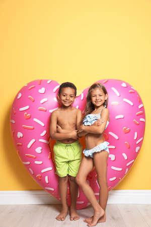 Cute little children with bright heart shaped inflatable ring near color wall Foto de archivo