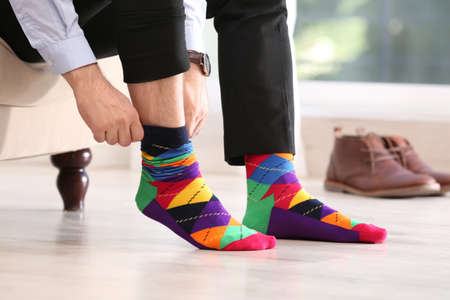 Uomo che indossa calzini alla moda al chiuso, primo piano