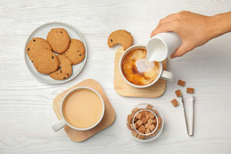 Woman pouring milk into cup with black tea on wooden table, top view