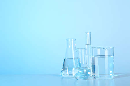 Laboratory glassware with liquid on table against color background. Chemical analysis Stock Photo