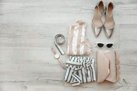 Flat lay composition with stylish female outfit and space for text on wooden background 写真素材