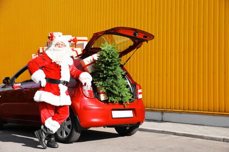 Authentic Santa Claus near red car with gift boxes and Christmas tree, outdoors