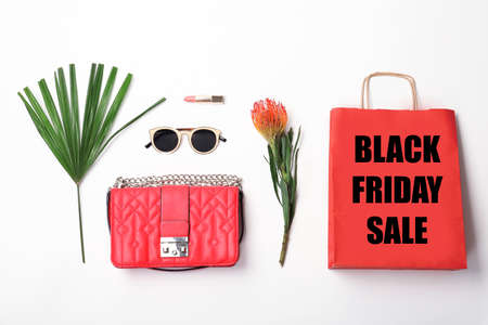 Flat lay composition with shopping bag and text BLACK FRIDAY SALE on light background
