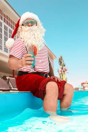 Authentic Santa Claus with cocktail near pool at resort