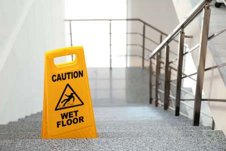 Panneau de sécurité avec phrase Attention sol mouillé dans les escaliers. Service de nettoyage