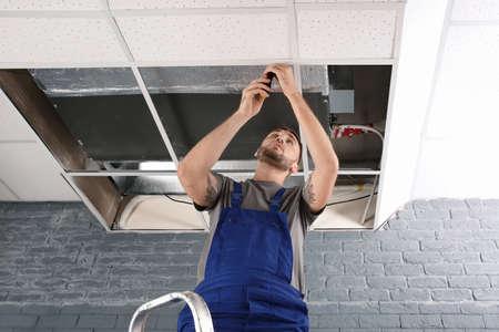 Młody mężczyzna technik naprawy klimatyzatora w pomieszczeniu