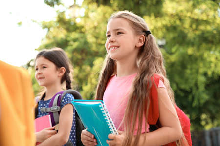 Cute little children with backpacks and notebooks outdoors. Elementary school