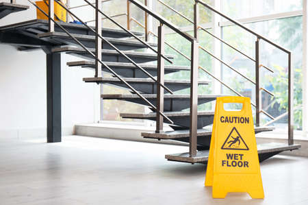 Safety sign with phrase Caution wet floor near stairs