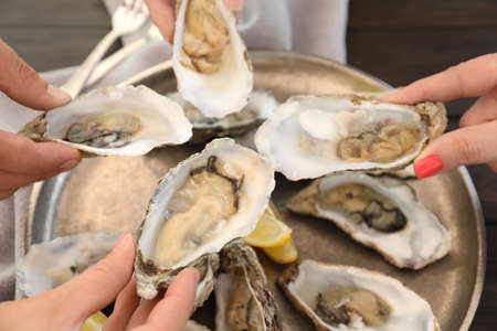 People with fresh oysters, focus on hands Stock Photo