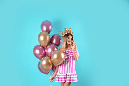 Young woman with crown and air balloons on color background
