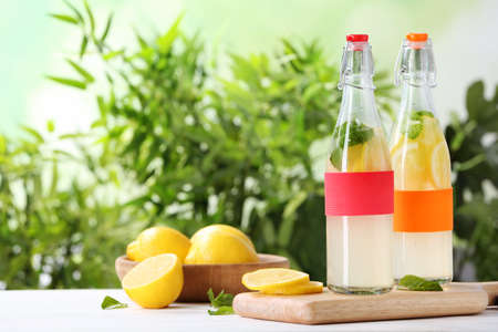 Bottles with natural lemonade on table against blurred background