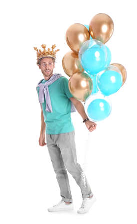 Young man with crown and air balloons on white background Foto de archivo