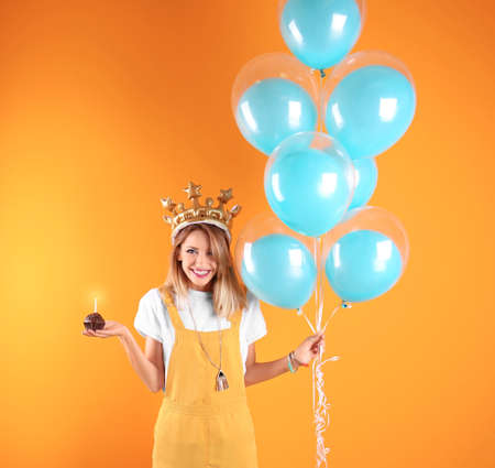 Young woman with birthday muffin and air balloons on color background