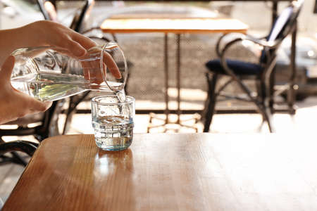 Woman pouring water into glass on wooden table indoors
