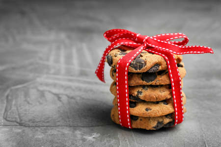 Stack of cookies with chocolate chips on grey background, space for text Archivio Fotografico