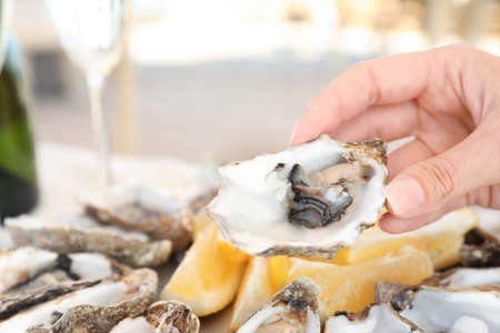 Woman holding fresh oyster over plate, focus on hand