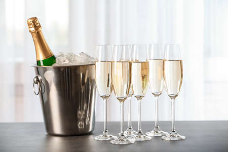 Glasses with champagne and bottle in bucket on table