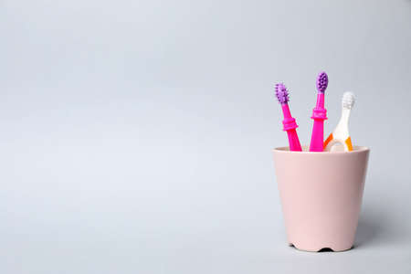 Baby toothbrushes in holder and space for text on color background 写真素材