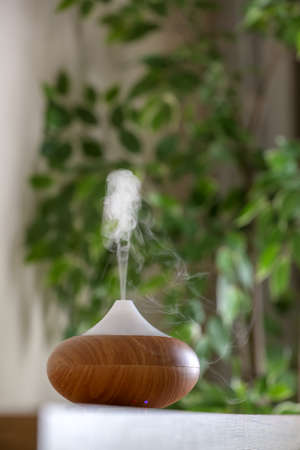 Aroma oil diffuser lamp on table against blurred background Stock Photo