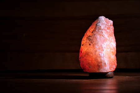 Himalayan salt lamp glowing on dark background with space for text