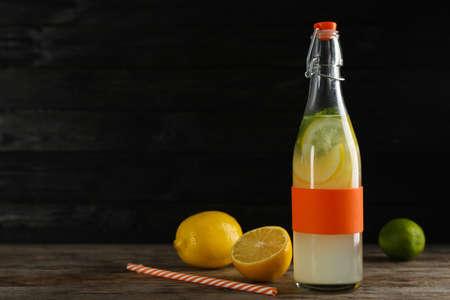 Bottle with natural lemonade on table against dark background