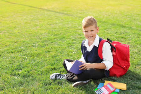 Schoolboy with stationery sitting on grass outdoors